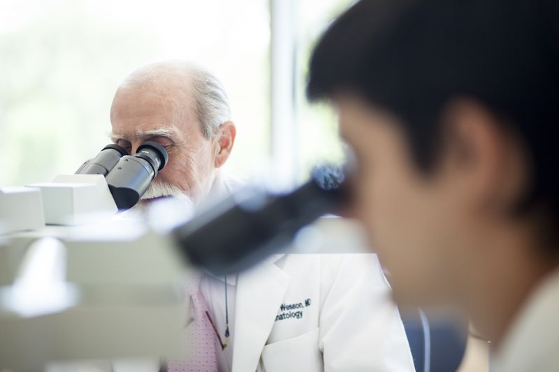 Dermatologists looking in a microscope